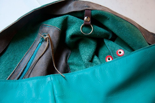 Turkusowa torba z konstrastowymi detalami.