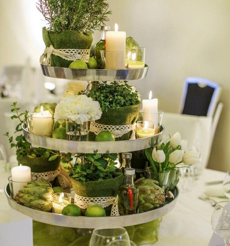 Kräuter, Limetten. weiße Blumen und Zierkohl auf dem Tortenständer arrangieren