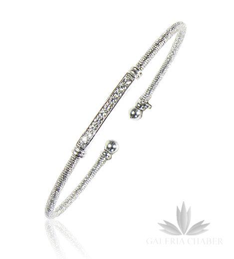 Bransoletka srebrna, rodowana w formie niepełnego kółka, wykonana z gęstej sprężyny. W centralnym punkcie motyw ozdobny, wysadzany cyrkoniami. Całość wykonana z dbałością o detale. Bransoletka dopasowuje się do każdego rozmiaru ręki, bardzo wygodna.