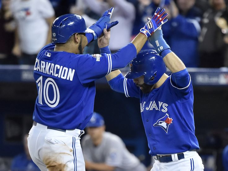 Toronto Blue Jays' Edwin Encarnacion (left) and Jose Bautista celebrate at home plate after scoring on a double by Troy Tulowitzki against the Kansas City Royals during sixth inning game 5 American League Championship Series baseball action in Toronto on Wednesday, Oct. 21, 2015.