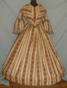 "Graceful 1860's Paisley Print Challis Dress & Matching Pelerine Collar.  Red & teal blue paisley stripe on cream background.  Pagoda sleeve & pelerine trimmed in silk fringe.  Cartridge pleated skirt, lined in cotton. Pelerine lined in cotton.  Front button closure.  Bust; 34""; waist: 28'; skirt length: 40"", hemline width: 124"". A few pea sized surface only holes, very light underarm discoloration, & few scattered age marks."