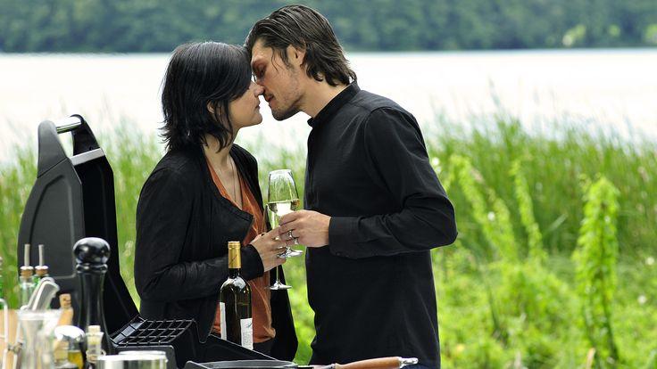 """""""Letzte Spur Berlin - Abgebrannt"""": Mina Amiri (Jasmin Tabatabai) und Nikola Orsic (Stipe Erceg) stehen sich gegenüber, die Köpfe nah beieinander kurz vor einem Kuss. Beide halten ein Glas Weißwein in der Hand. Sie stehen neben einem Grill. Im Hintergrund sind Wiese und Wasser zu sehen."""