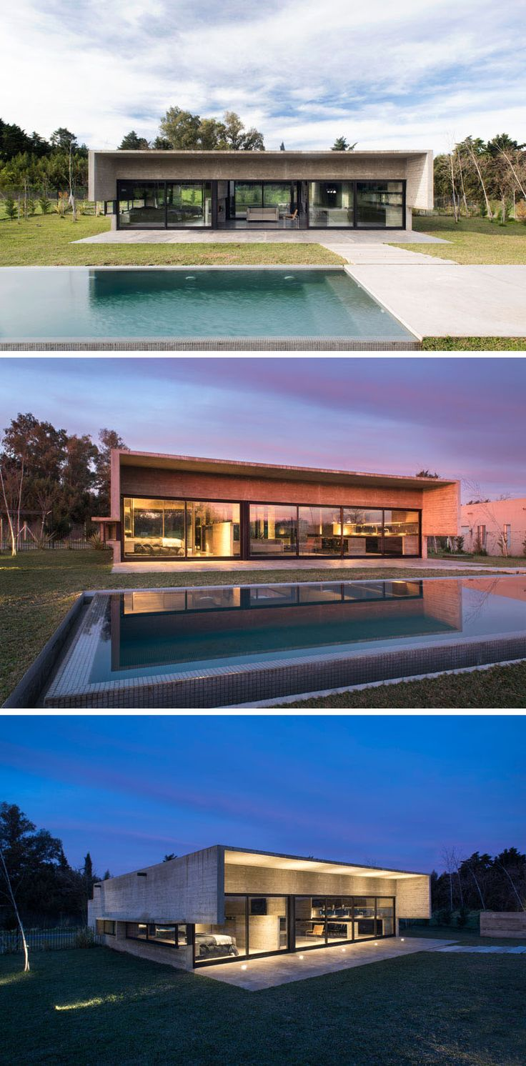 At the rear of this modern concrete house, the roof line extends out over a patio and provides some sun protection, while a path leads up to the swimming pool. A night, lighting shows off the design of the home and highlights the overhang. #ConcreteHouse #SwimmingPool #ModernHouse