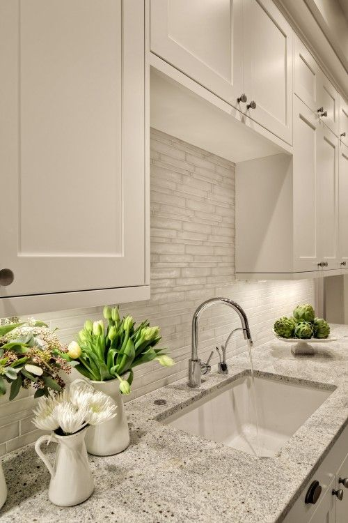 Light countertop with white cabinets. Alternative backslash to subway tile. Faucet style.