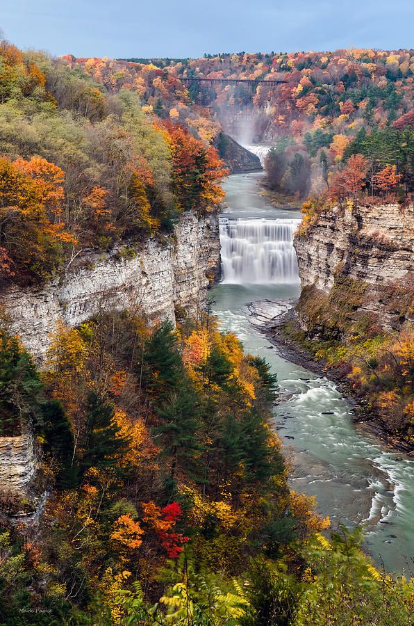 """Middle Falls Of Letchworth State Park Letchworth State Park, renowned as the """"Grand Canyon of the East,"""" is one of the most scenically magnificent areas in the eastern U.S. The Genesee River roars through the gorge over three major waterfalls between cliffs--as high as 600 feet in some places--surrounded by lush forests. Hikers can choose among 66 miles of hiking trails."""