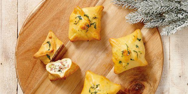 Kerstpakketjes met gerookte spekreepjes, bosuitjes, roomkaas, blauwe kaas, mozzarella, zongedroogde tomaatjes, basilicum, tijm en rozemarijn.