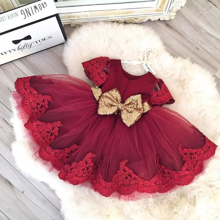 A lovely burgundy tulle and lace dress with a gold bow - perfect for any special occasion! This Burgundy Party Dress is offered by Itty Bitty Toes, Children's boutique shop!