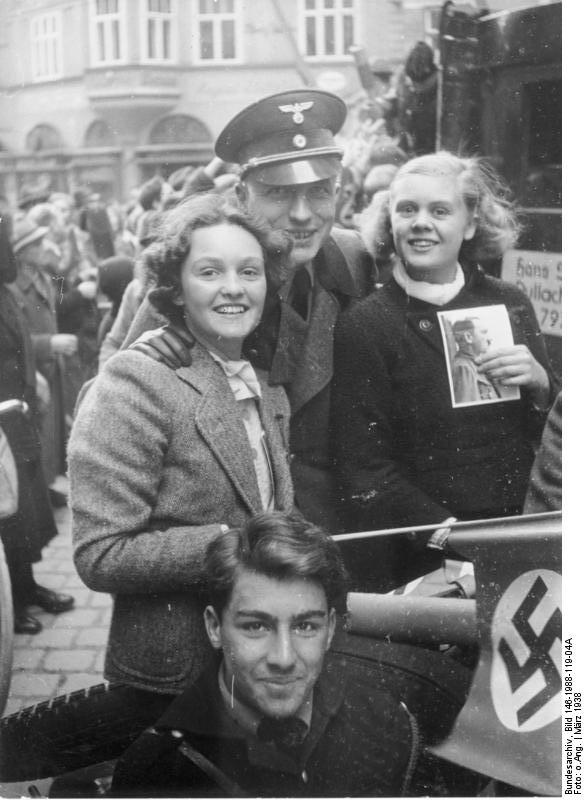 """Anschluss Österreich (Union of Austria [with Germany]), Salzburg, March 1938: The original German caption reads: """"On Saturday, when the German troops marched into Salzburg, the entire population was at a frenzy of enthusiasm. Everywhere you looked [you saw] radiant faces, and many people carried portraits of the Fuehrer, and almost all were waving swastika flags."""" At least, the propaganda writer left an """"almost"""" in there."""