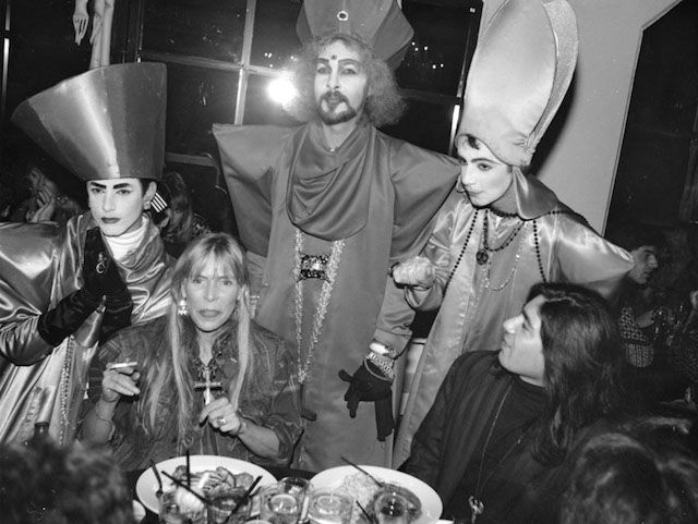 The undated photo, which was taken by Gary Leonard, shows Mitchell at Vertigo nightclub, seated beside a poet named Joaquine. Standing behind her, according to the library archive, are the Voguing Popes: Bret Boreman, Steven Arnold and J.V. McCuley.