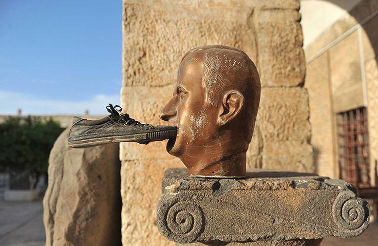 Idlib, Syria: A shoe is glued to a statue of Hafez al-Assad
