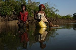 Ndra Lopes and Teresa Jaoquim wade through the water