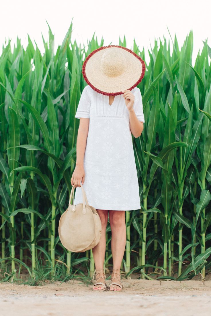 the perfect, simple summer outfit with a white linen dress, round woven bag, neutral lace up flats and a straw sun hat.