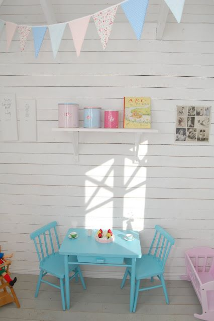 Love the white walls and coloured furniture and bunting