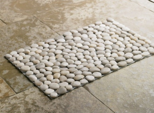 """Smooth river stones in neutral tones add natural beauty and functional appeal to a mat that can be used next to a door or beside a shower. The mat is assembled from hand-gathered stones and securely attached to a weather tough backing. Each is unique, wonderfully tactile under foot, and artfully composed, as in a mosaic."""