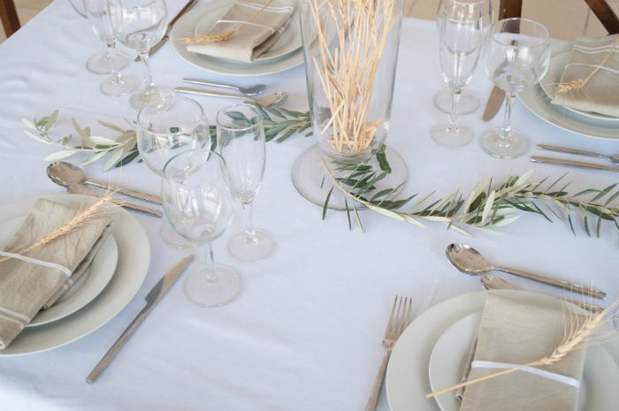 A Mediterranean table setting with olive branch table runner