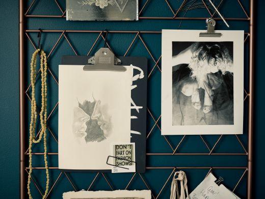 Selbst gemachte Inspirationstafel aus Metalldraht, die mit Lederriemen an der Wand befestigt wurde.