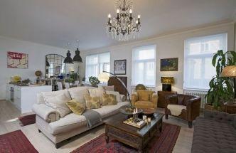 Hlavní prostor je zařízen kombinací klasického nábytku, kousků vestylu etno azcela bílé kuchyně spovrchem vbílém laku. Mnoho předmětů si majitelka přivezla zčetných cest, například koberce pocházejí zDagestánu