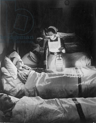 A nurse holding a lamp as she visits patients on a ward at Westminster Hospital, December 1940 ~