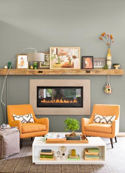 A mid-tone shade of gray highlights the wall surrounding this fireplace and brings out the yellow of the chairs and all the accent colors used in the paintings and accessories.
