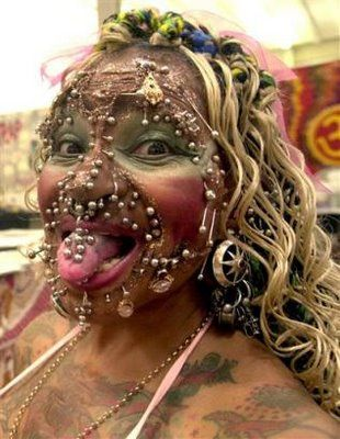 In total, brazilian Elaine Davidson has the most number of tattoos and over 2500 piercings on her body, both internally and externally, approximately 500 just around the genitals. the total extra weight she carries due to this obsession comes to around 3kg and she is thankfully the most pierced person in the world. now living in edinburgh she claims to be too scared to go home to brazil due to the attention she'd attract possibly resulting in some kind of attack
