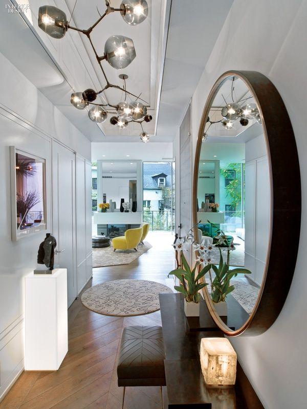 A mirror by Tyler Hays reflects a custom chandelier by Lindsey Adelman in the entry, which also connects private spaces to the living area.