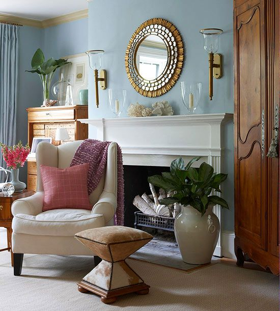 Dress up your fireplace wall with a pair of wall sconces, one mounted on each side of the fireplace, with a round mirror in the middle.
