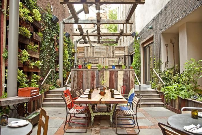 Patio + Backyard Idea: pergola overhead is cantilevered, made from a reclaimed truss / simple planter box wall / mismatched garden chairs