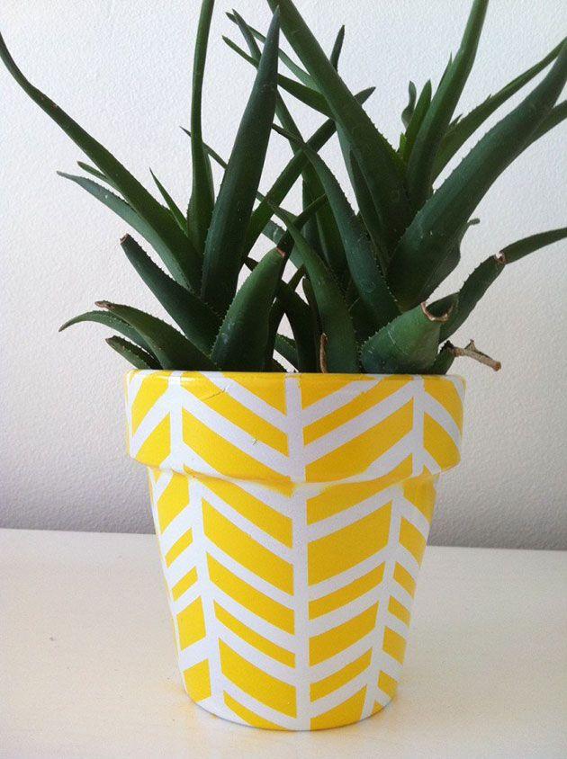 Macetas de barro pintadas en amarillo y blanco