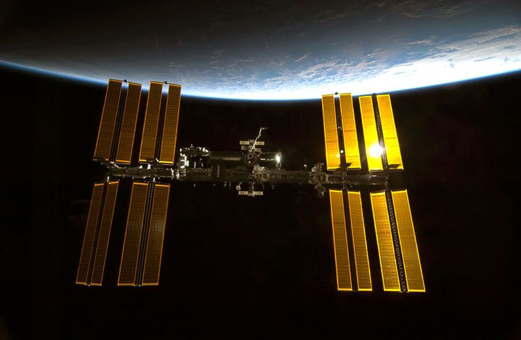 Sunlight glints off the International Space Station with the blue limb of Earth providing a dramatic backdrop in this photo taken by an astronaut on the shuttle Endeavour just before it docked after midnight on Feb. 10, 2010 during the STS-130 mission.