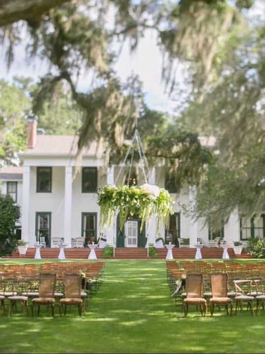 Outdoor wedding ceremony with beautiful floral chandelier on front lawn of the Southwood House in Tallahassee, Florida. Event design and florals by Over the Moon Events in Orlando, Florida