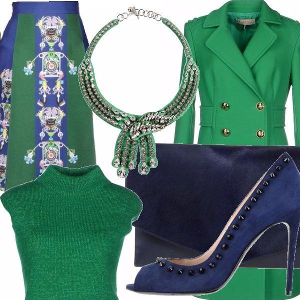 Longuette a pannelli con stampa astratta verde e blu, dolcevita a maniche corte verde, cappotto con cintura in vita e bottoni color oro, decolleté blu con bochiette, collana verde con strass bianchi, borsa a mano in pelle blu
