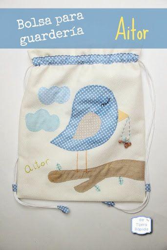 Mochila para guardería con un pajarito en tonos azules y el nombre bordado a mano.