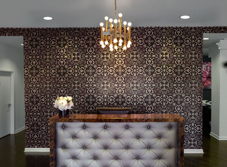 """""""Our modern, comfortable waiting area encourages guests to interact with retail or lounge with the iPad we provide. We think the desk and wallpaper are quite sexy and make a statement of true distinction."""""""