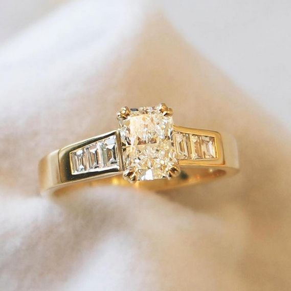 Naveya & Sloane bespoke octagonal diamond centre stone, set in a split claw basket. Crafted in 18k yellow gold, with trapezoid diamonds channel set into the band.