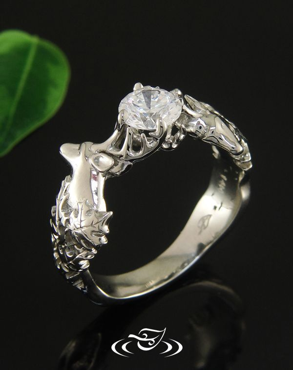 A white gold white tail deer's antlers hold a round brilliant cut Canadian diamond. This #EngagementRing features carved and pierced  maple and oak leaf design on shoulders and tapers to tree trunk texture. #GreenLakeJewelry #Deer