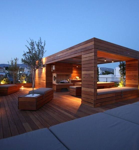 Outdoor entertaining whatever the weather! We love the integral seating in the open sides of this outdoor kitchen, and the dramatic lighting too.  Picture credit: http://www.thekitchendahab.com/  #outdoorkitchen, #exteriordecking, #rooftopterrace