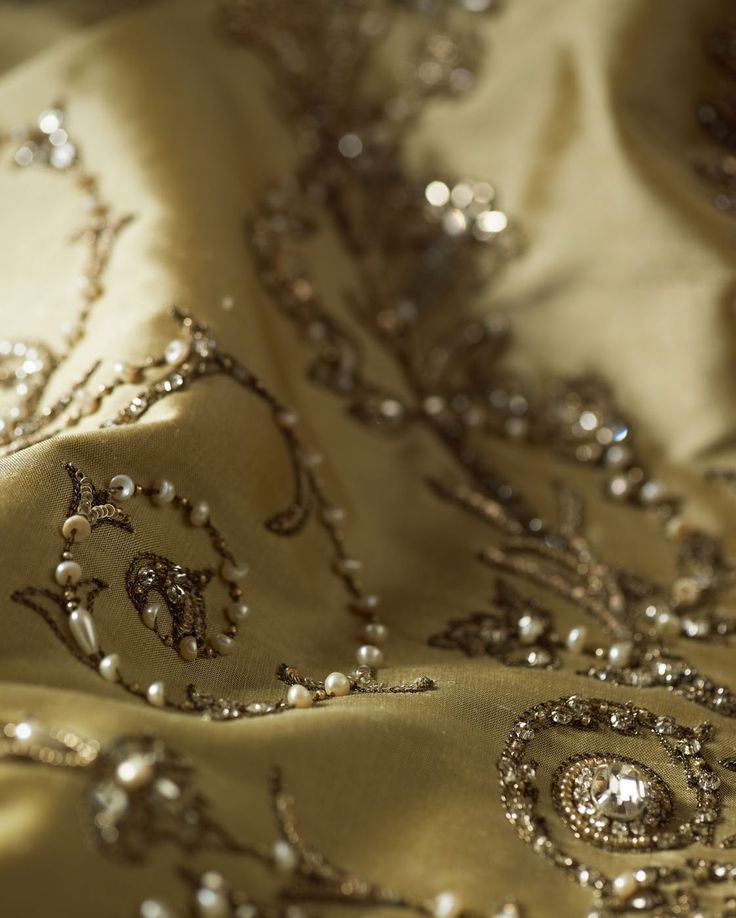 Capriccio is a flamboyant couture fabric design in an early 18th century style. It depicts ornately framed vases of flowers, delicately adorned with seed pearls and crystals. Pictured here on Silk, Cameo.