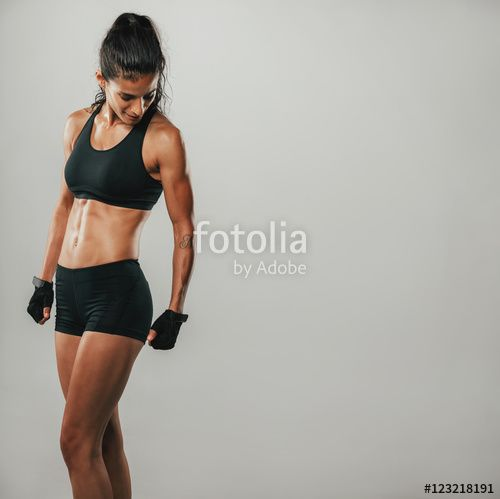 Muscular woman in black sports shorts and top