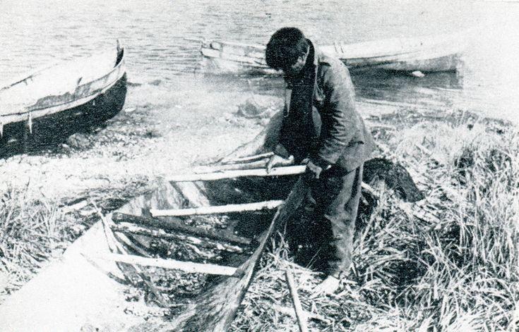 """Hombre alacalufe separando los dos lados del casco en la fabricación de una canoa. Fotografía Joseph Emperaire. 1950 aprox. En: """"Los Nómades del Mar"""". Joseph Emperaire. Ediciones de la Universidad de Chile. 1963."""