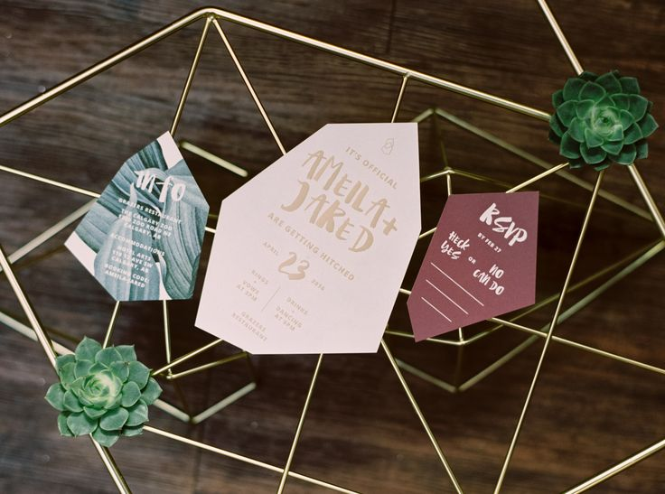 Geometric shaped wedding invites in gold and fig colors.