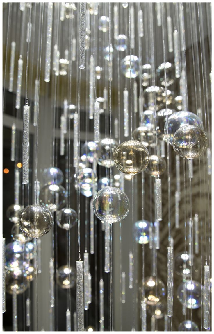 Modern chandelier made of hand blown glass and crystals hanging on sparkling fiber optics. Detail.