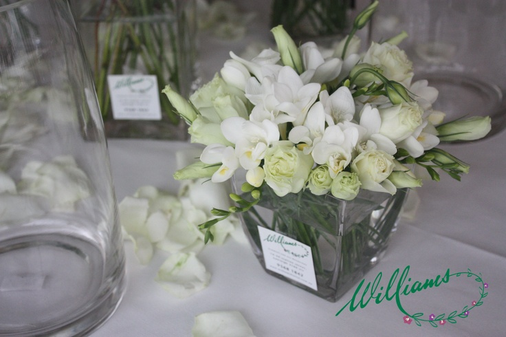 a small vase of white freesias, lisianthus and greenery.