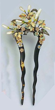 Baroque pearl, diamond, and enamel hair pin on tortoiseshell tines. Mounted in silver and gold.