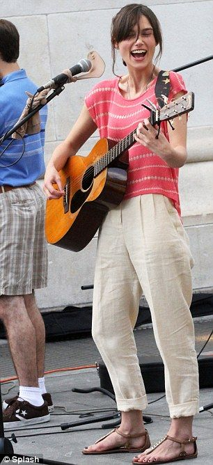 Keira Knightley strums an acoustic guitar on the New York set of Can A Song Save Your Life? Keira was clearly getting stuck in to her strumming; laughing and smiling as she filmed scenes on the city's streets. The 27-year-old star showed off her slim figure in in a pink and cream T-shirt  which she teamed with beige trousers and brown sandals as she joined a group of musicians for a singalong. via dailymail.co.uk