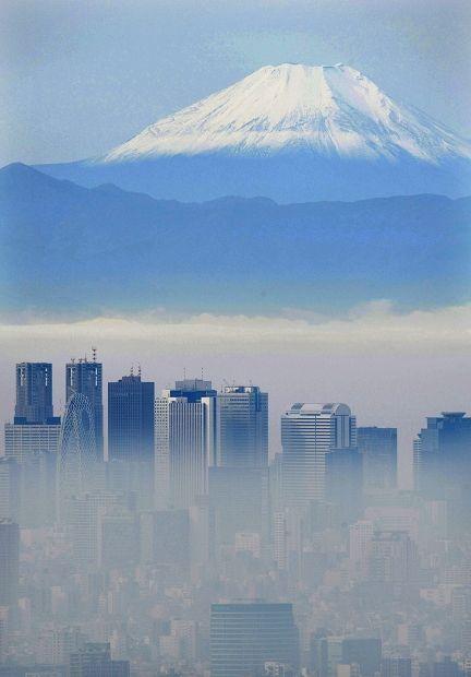 かすみでかすむ新宿の高層ビル群と富士山=2015年11月24日午前9時8分、本社ヘリから猪飼健史撮影