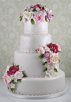 This cake was designed for a wedding in the garden of a cottage at the foot a mountain. Reproduced in sugar flowers bridal bouquet roses, peonies, tulips and jasmine. A cake romantic yet sophisticated with pearls and lace detail a little sugar, The flavor was chosen Belgian chocolate cream filled with violets and berries.