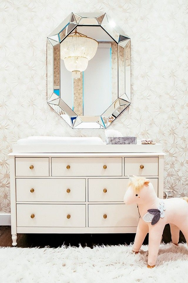 Glam nursery with floral wallpaper, a silver mirror, and a white dresser