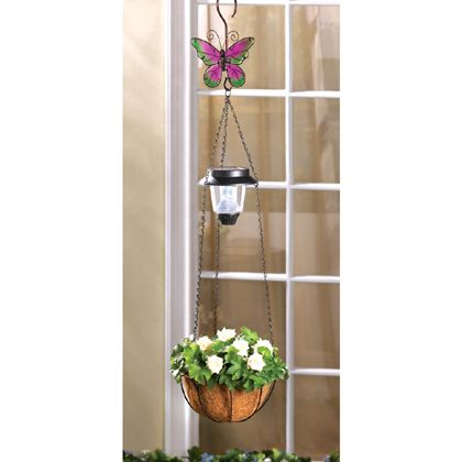 """With a solar light, planter basket and beautiful stained glass butterfly, this hanging decoration is a triple treat! Classic wrought-metal with fiber basket adds a timeless splash of color to your outdoor decor.Solar panel at top. Weight 1 lb. 8 1/4"""" diameter x 29 1/2"""" high. Iron, plastic and coconut fiber. Plant not included."""