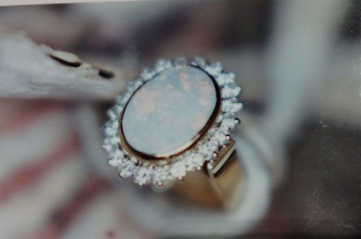 Rim set milk opal surrounded by a frame of diamonds claw set in a wire basket supported on a flat flow up band
