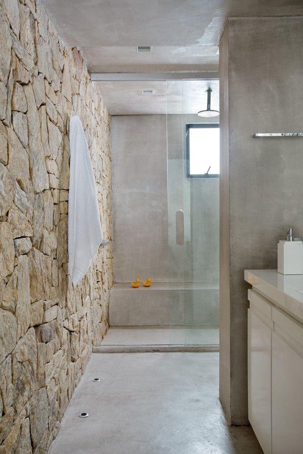 Banheiro da suíte | A parede revestida de pedra madeira é a atração do espaço, bem amplo. No boxe, banco de alvenaria (Foto: Denilson Machado/MCA Estúdio)